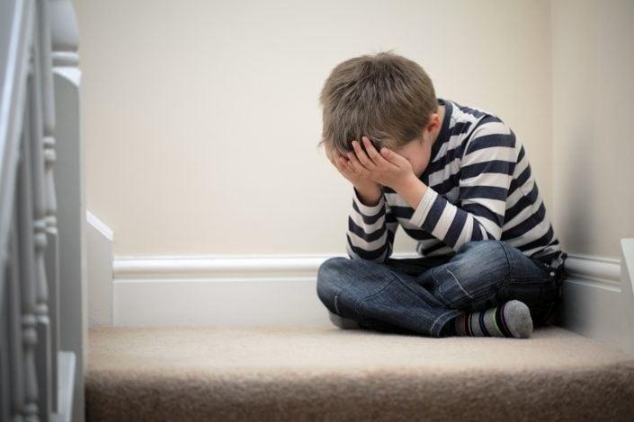 Obraz chłopca zakrywającego twarz rękoma w geście załamania i smutku i zazdrości.
